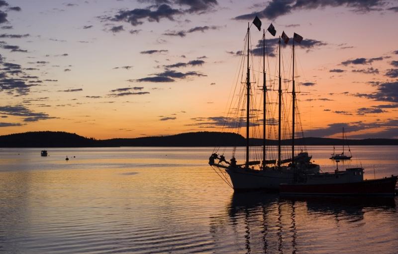Colorido atardecer con la silueta de un velero de 3 mástiles atracado en el Parque Nacional Acadia