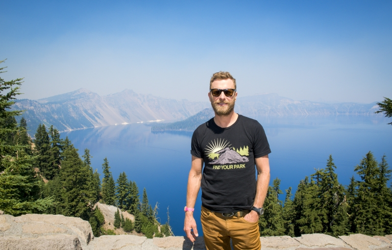 Dierks Bentley vistiendo una camiseta negra de Find Your Park frente al Parque Nacional Crater Lake