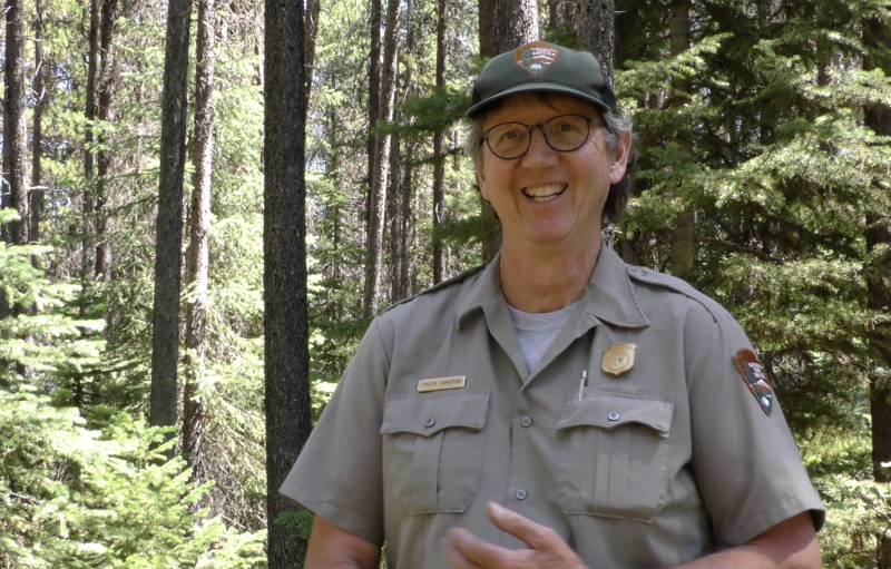Backcountry Ranger Chuck Cameron smiles at a camera, surrounded by tall, thin green trees at Glacier National Park
