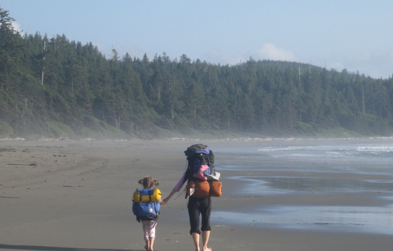 Child and adult with big backpacks walking down a sandy beach next to an evergreen forest at Olympic National Park