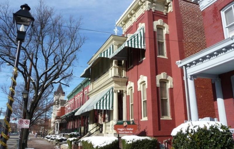 Casa victoriana de ladrillo rojo con toldos blancos y verdes en invierno, la acera bordeada de arbustos de hoja perenne cubiertos de nieve