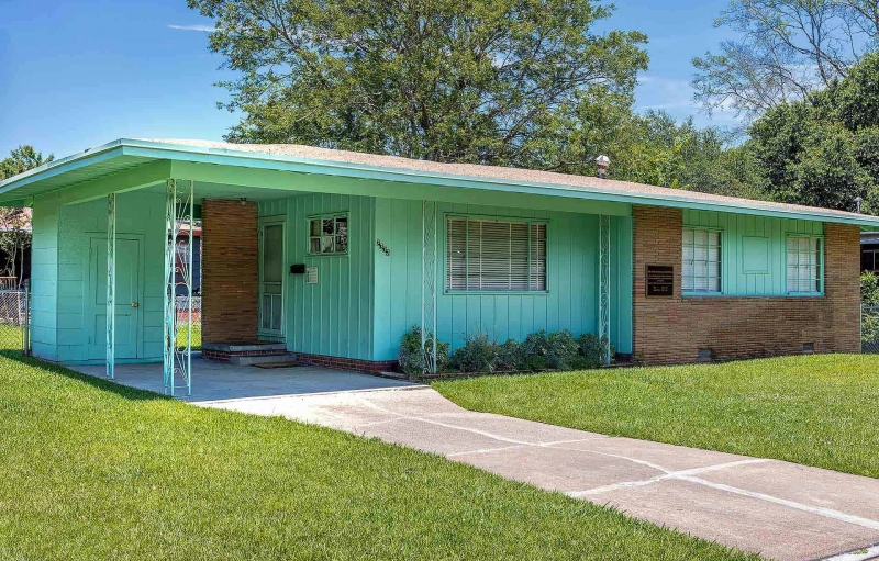 A single-story ranch-style house with light brown brick and teal siding.