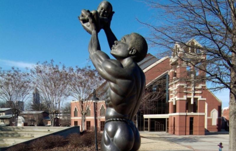 Estatua de un hombre con un bebé pequeño hacia el cielo