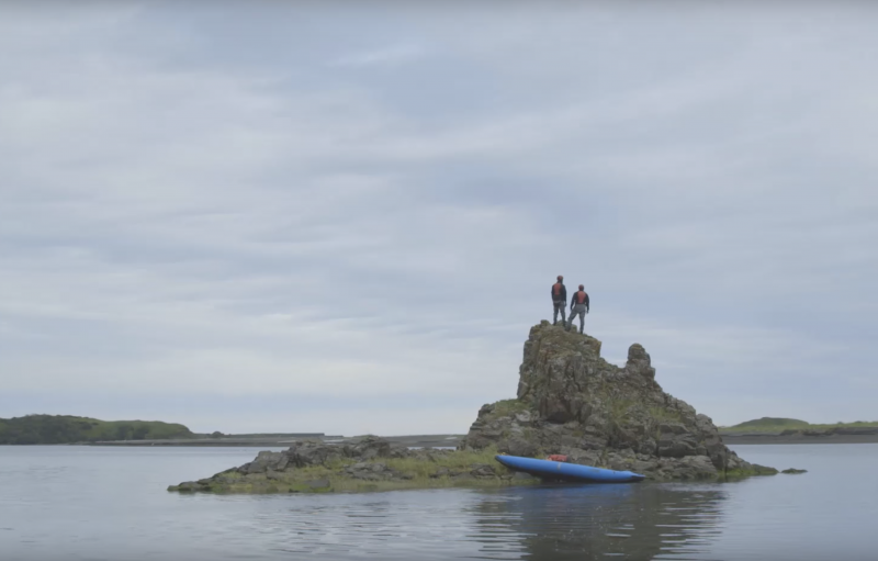 Two guys standing on a rock island
