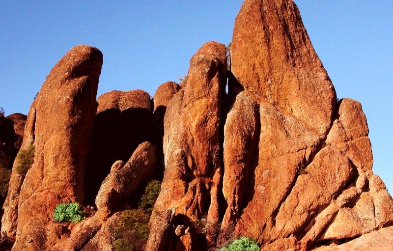 rocas de color rojo brillante sobresalen hacia arriba desde el suelo hacia el cielo