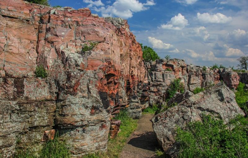una pared de roca de color rojo con las nubes mullidas blancas en un cielo azul