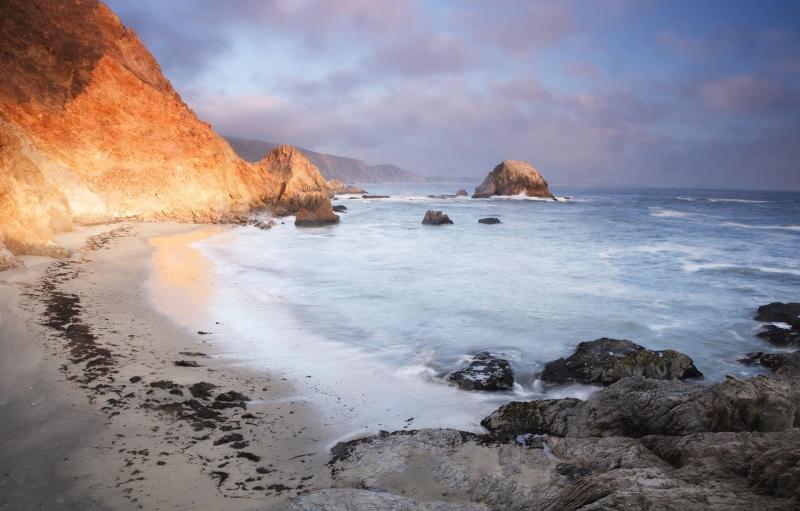 sol brilla en la playa agreste donde océano se encuentra ladera de la montaña