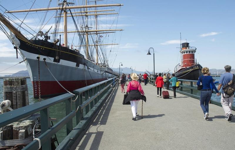 viejo barco atracado en el muelle, el barco tiene mástiles, pero sin velas, la gente camina en el embarcadero
