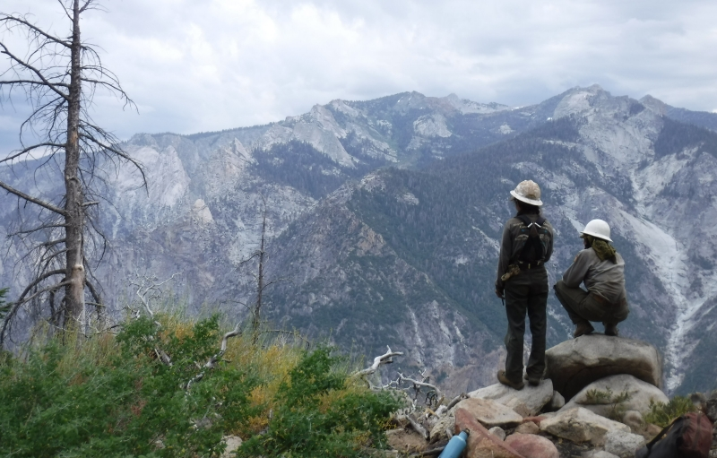Two people standing on rocks overlooking a valley with mountains in the background at Sequoia & Kings Canyon
