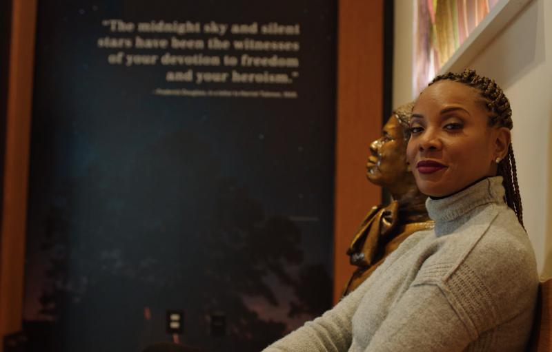 Una mujer sentada en un banco junto a una estatua de Harriet Tubman
