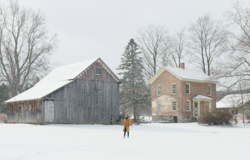 Un visitante camina en la nieve entre un granero y un edificio de ladrillo de dos pisos.