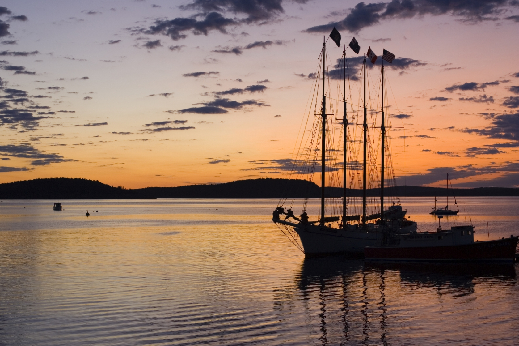 Colorful orange and purple sunset with the silhouette of a 3-masted sailboat docked at Acadia National Park
