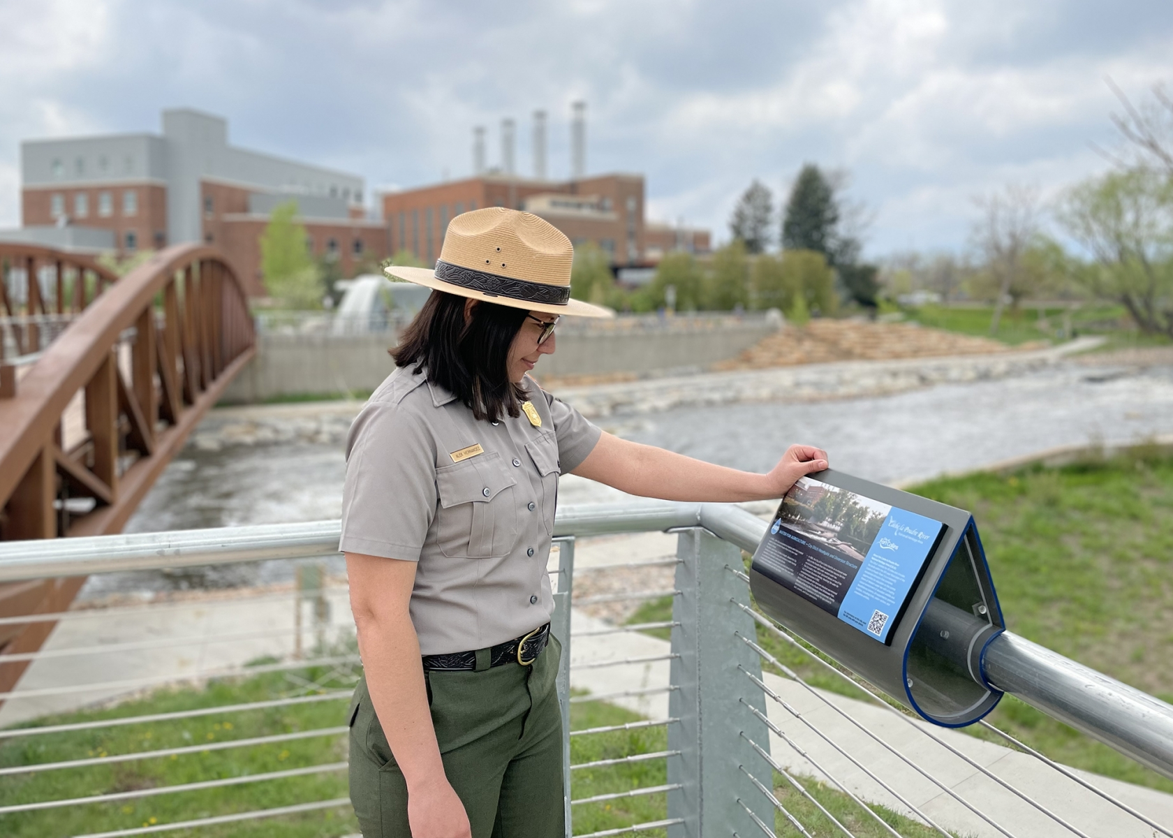 Alex Hernández se encuentra junto a una exhibición a lo largo de un río.