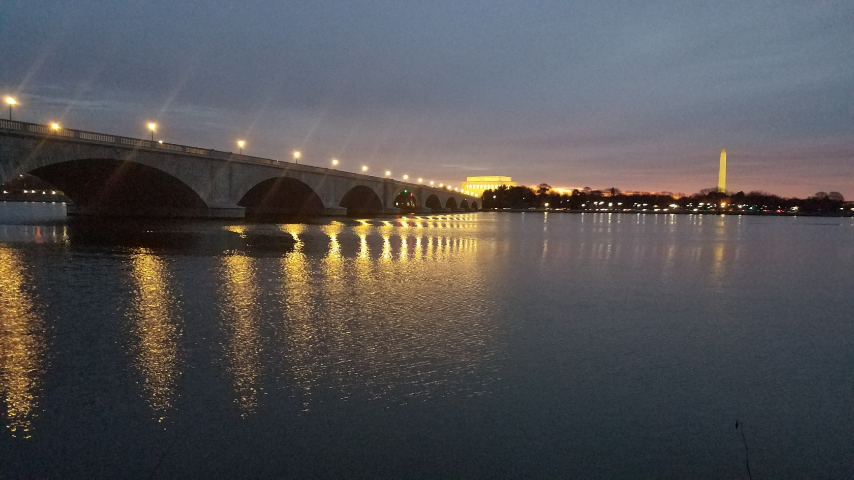 Arlington Memorial Bridge dim light with lights reflecting off of water and memorials in the distance