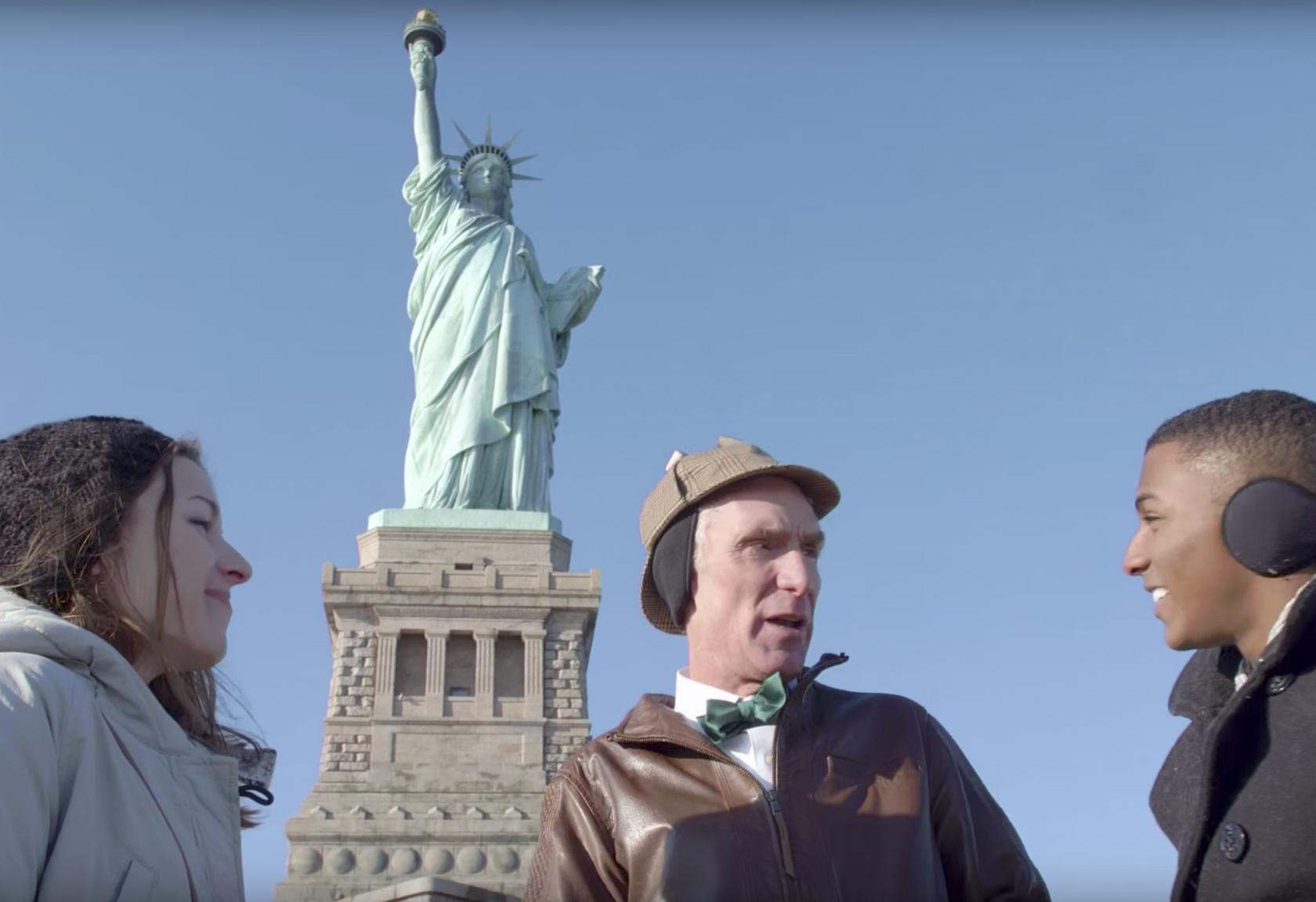 Bill Nye with two other people standing in front of the Statue of Liberty