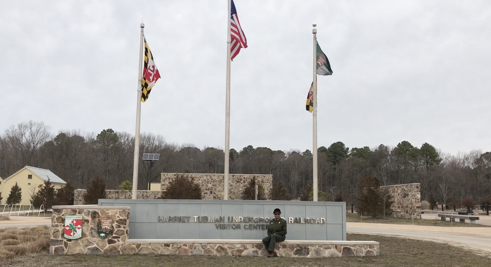 Deanna Mitchell sits outside on a stone sign for the Visitor Center at Harriet Tubman Underground Railroad National Historical Park. Three flags wave gently on flagpoles behind the sign.