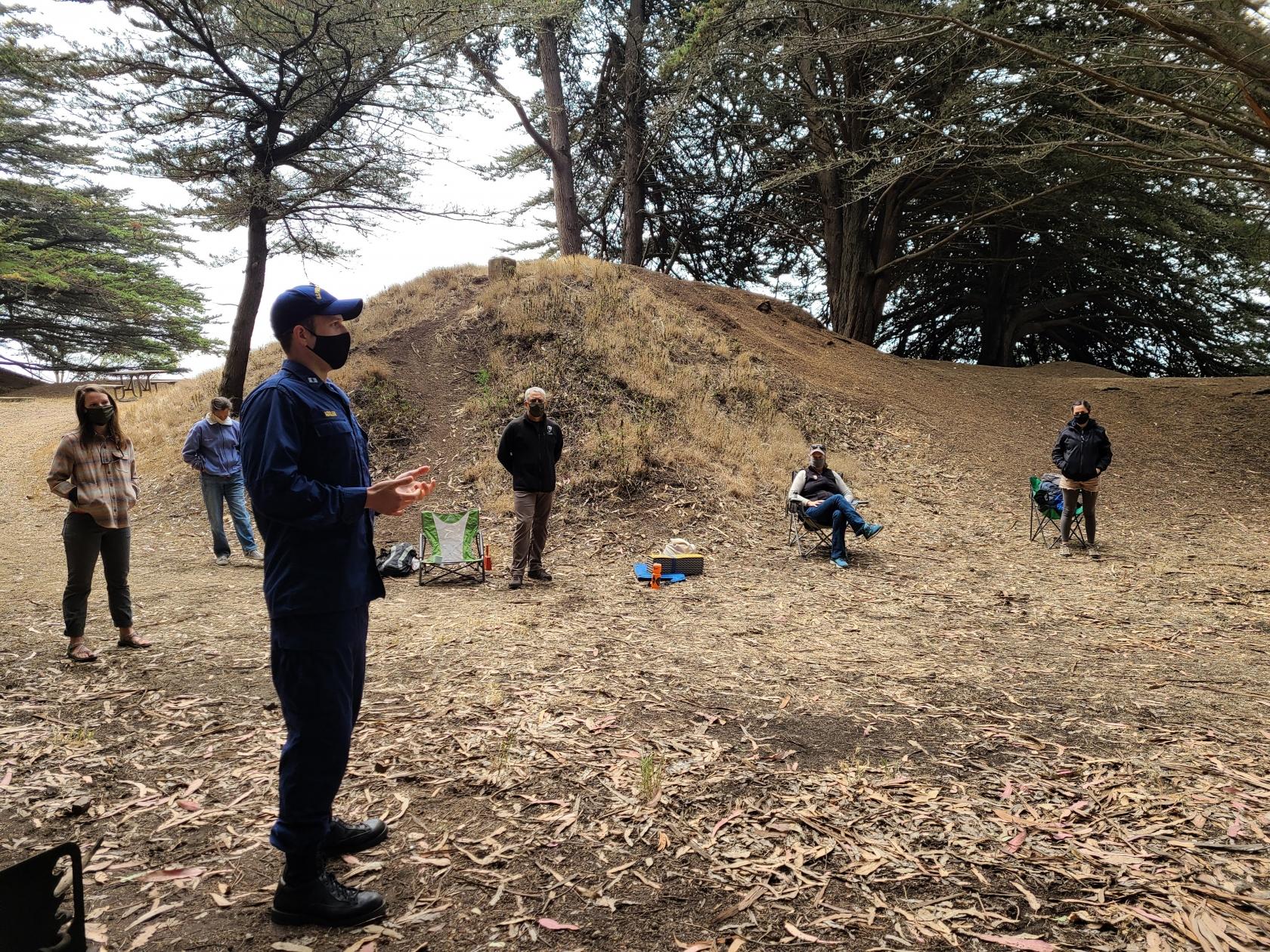 LCDR Matt Kozler, con una máscara, habla con un grupo de personas, también con máscaras y de pie lejos el uno del otro.