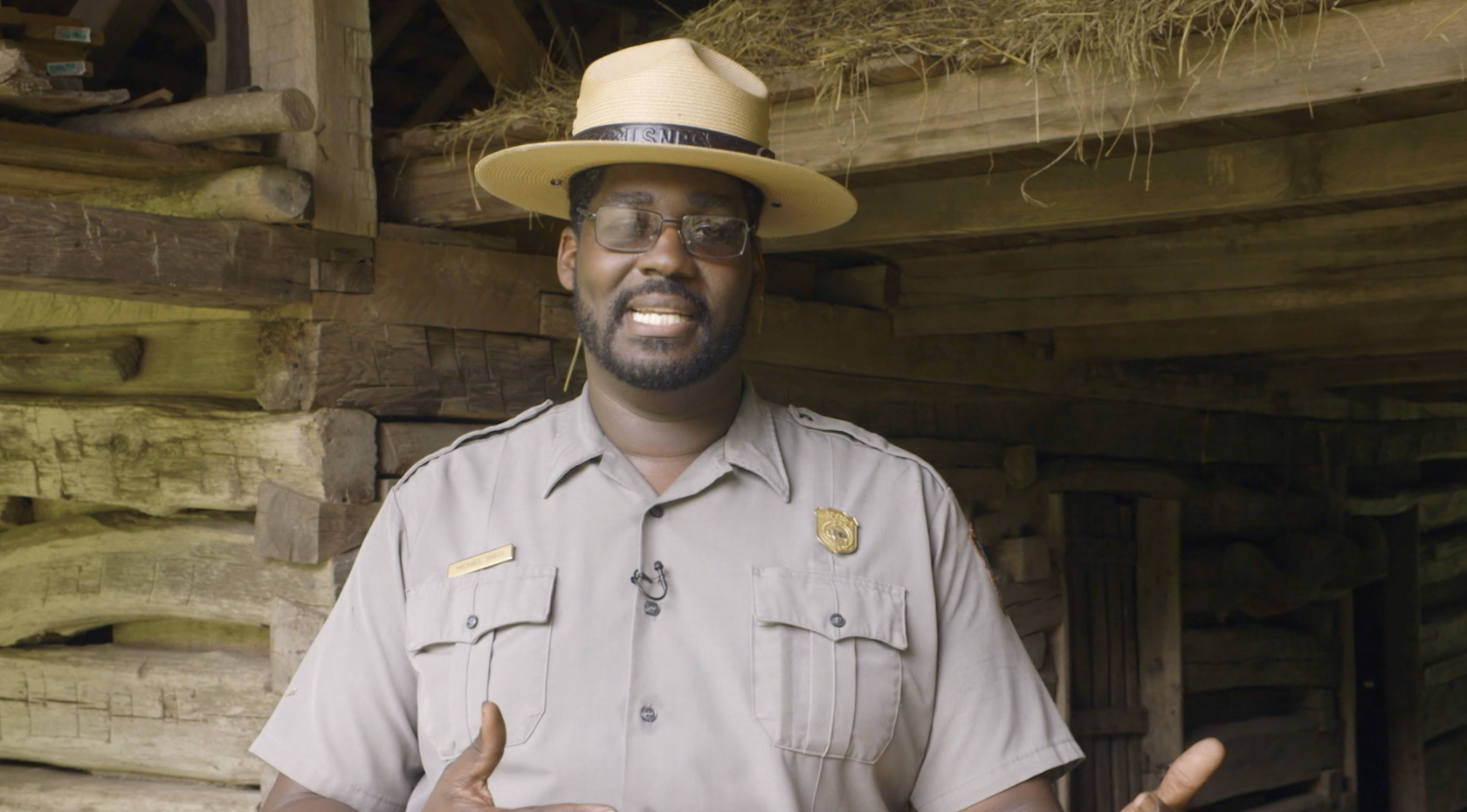 NPS employee Michael Smith stands in uniform and smiles at the camera