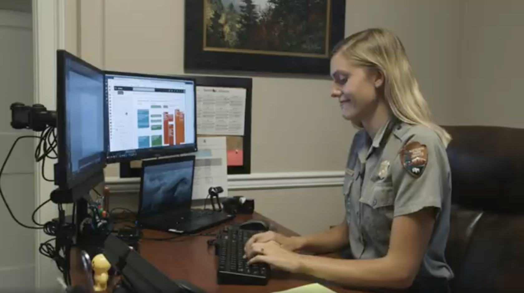 Jessie Snow, in NPS uniform, works at a computer