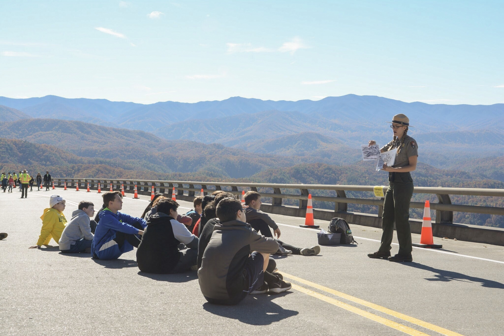 On a paved road, blocked off to traffic, Jessie Snow, in full NPS uniform, holds up a couple of papers to give a demonstration to a group of students sitting on the road in front of her. In the background, a scenic vista of the Great Smokies