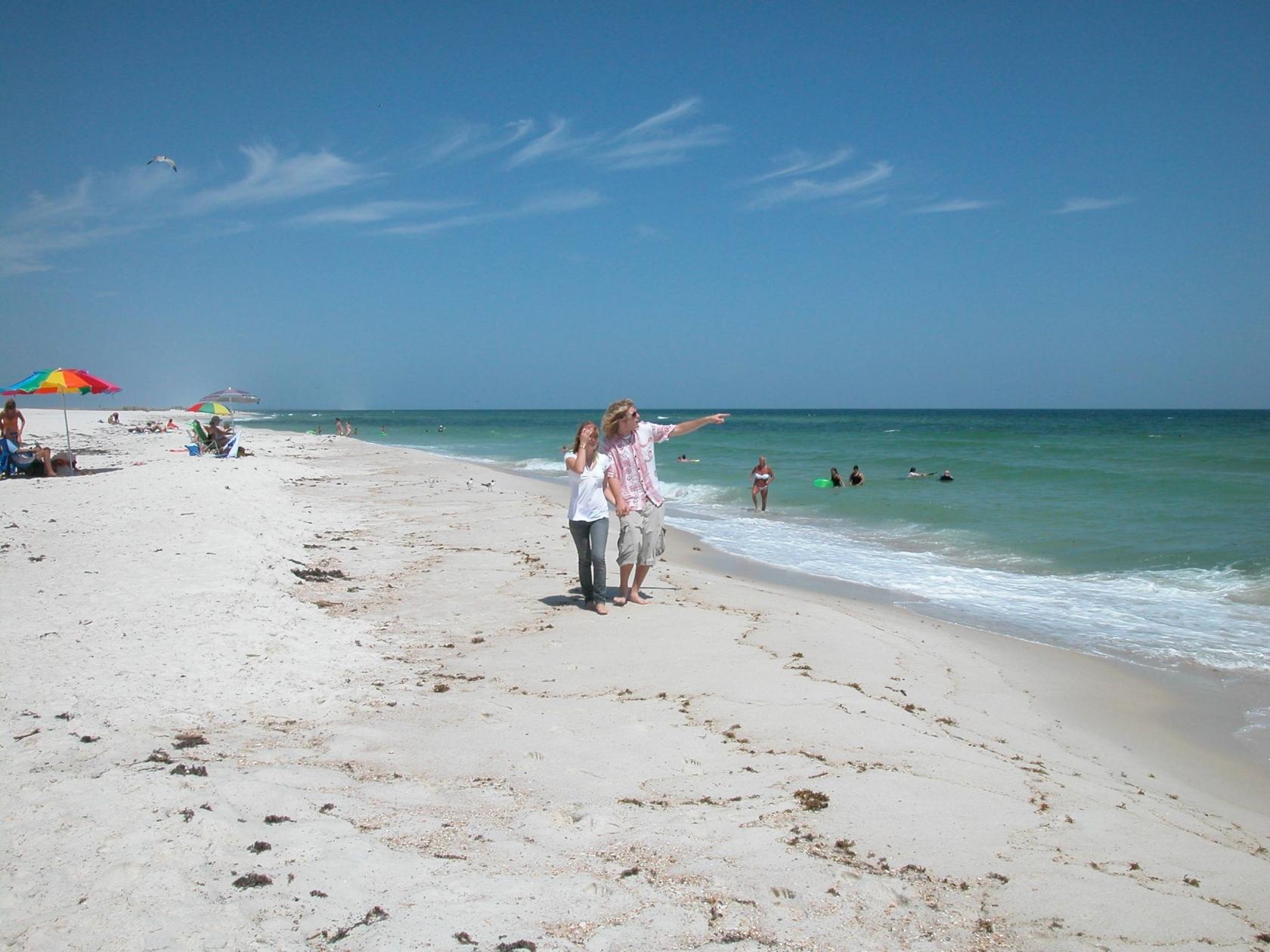 Mujer que camina al lado de un hombre que apunta hacia el océano mientras caminaba por la playa de arena de la costa nacional de Islas del Golfo