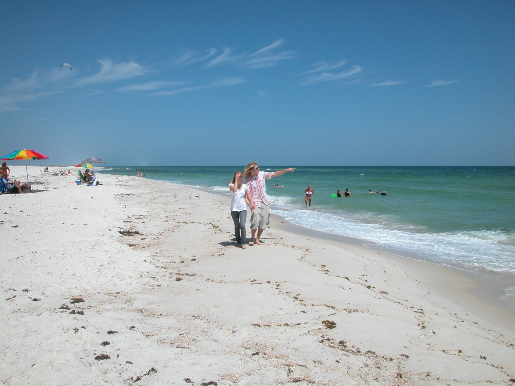 Woman walking next to a man pointing out to the ocean while walking on the sandy beach of the Gulf Islands National Seashore