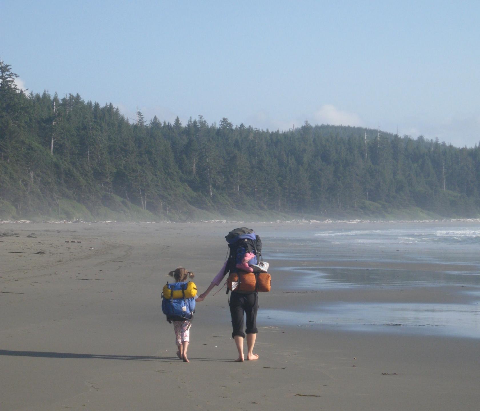 Niños y adultos con grandes mochilas caminando por una playa de arena junto a un bosque siempre verde en el Parque Nacional Olympic