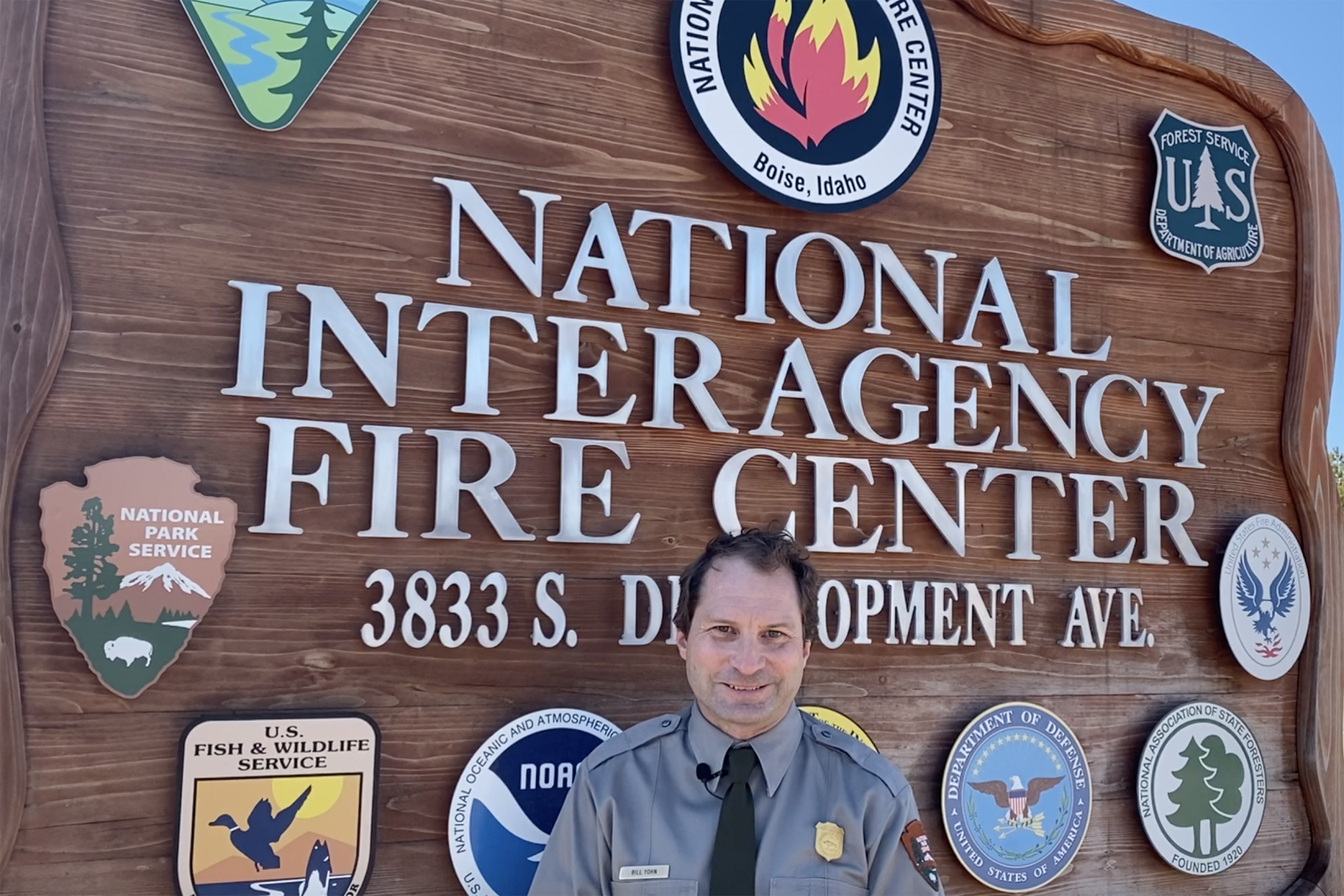 Bill Yohn poses in front of the sign at the National Interagency Fire Center