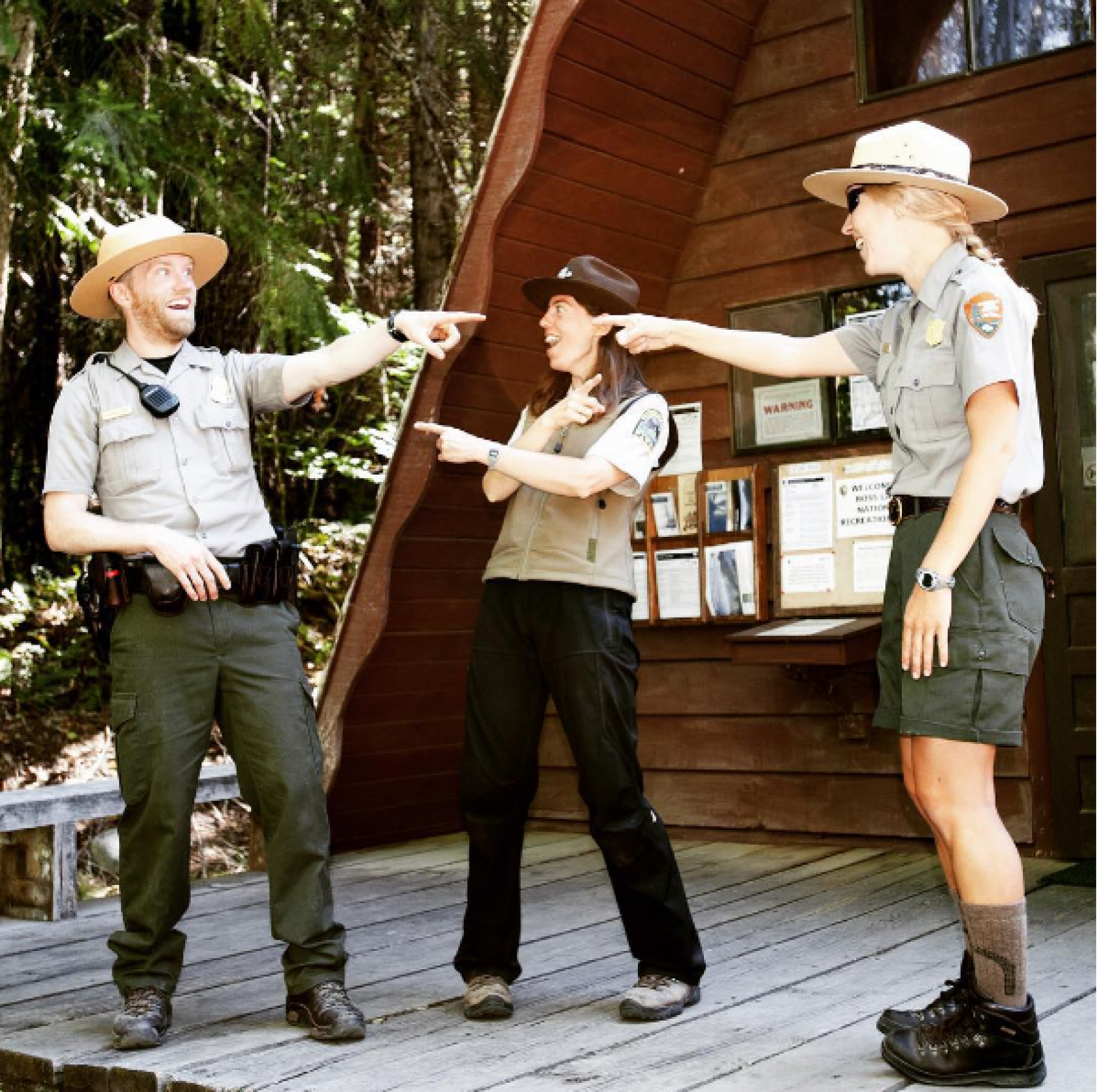 Three park rangers laughing and point at each other in front of a forest lodge