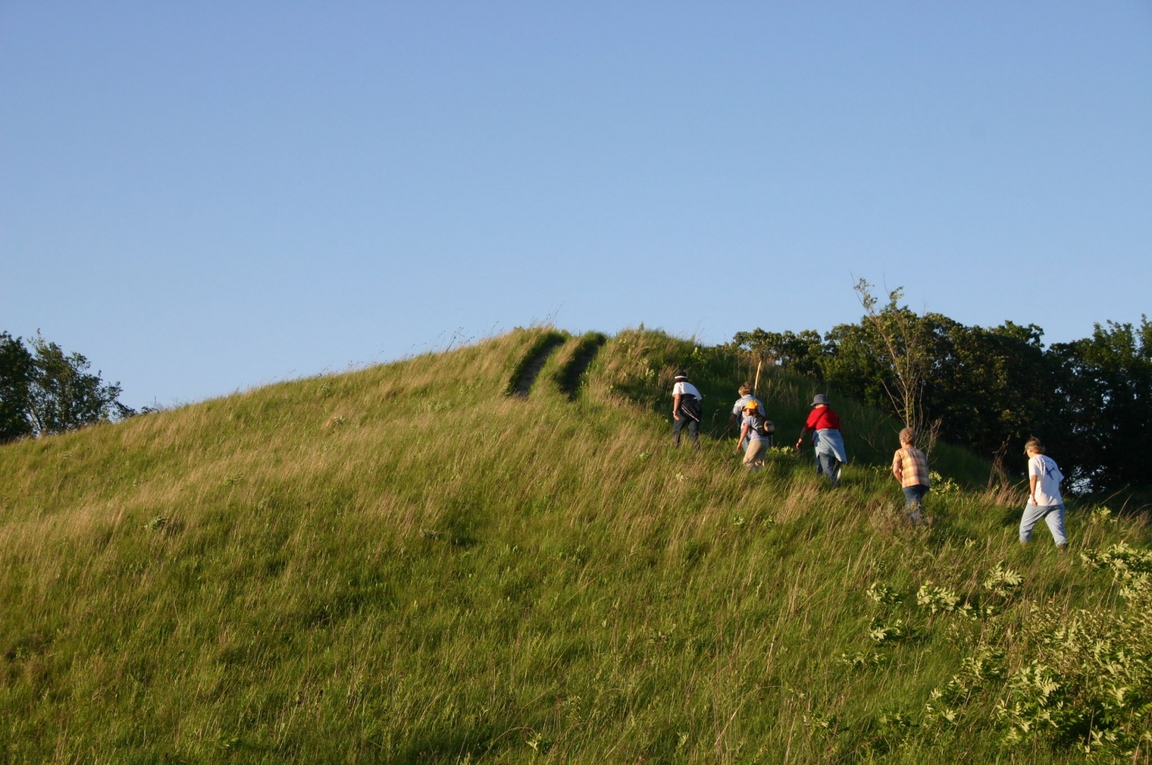 5 people hiking up a trail on grassy hill with blue skies along the Lewis & Clark National Historic Trail