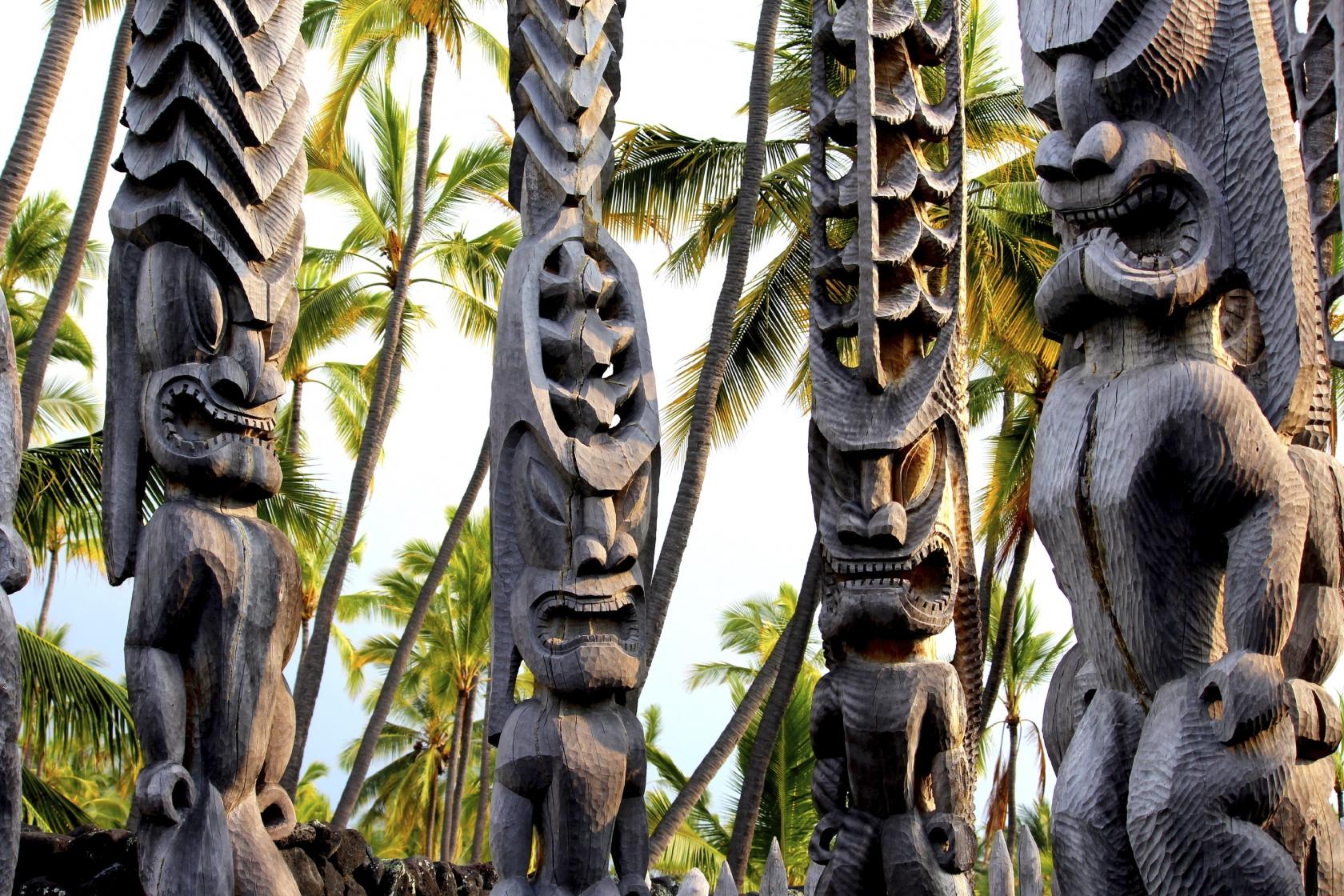Cuatro tótems de madera con el sol que ilumina las caras talladas en el Parque Nacional de Pu'uhonua