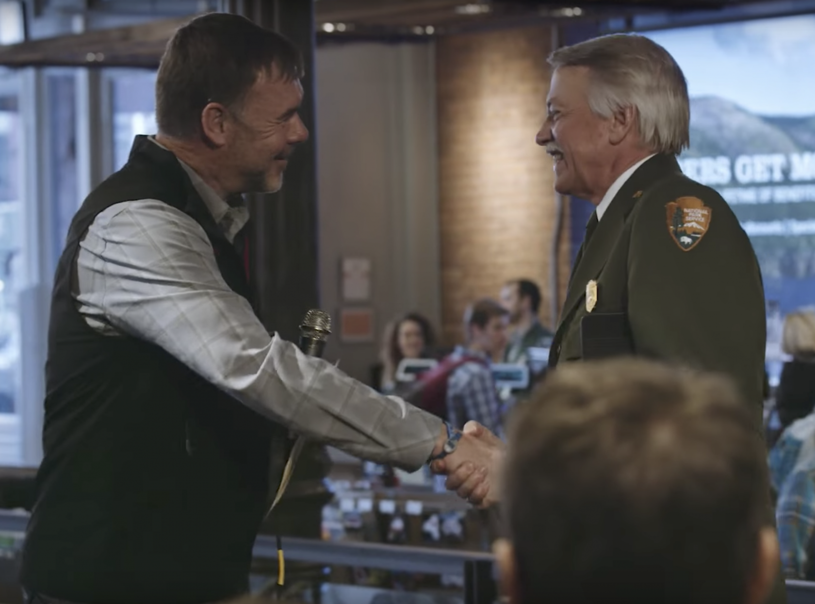 An REI employee shaking hands wit the former National Park Service Director John Jarvis