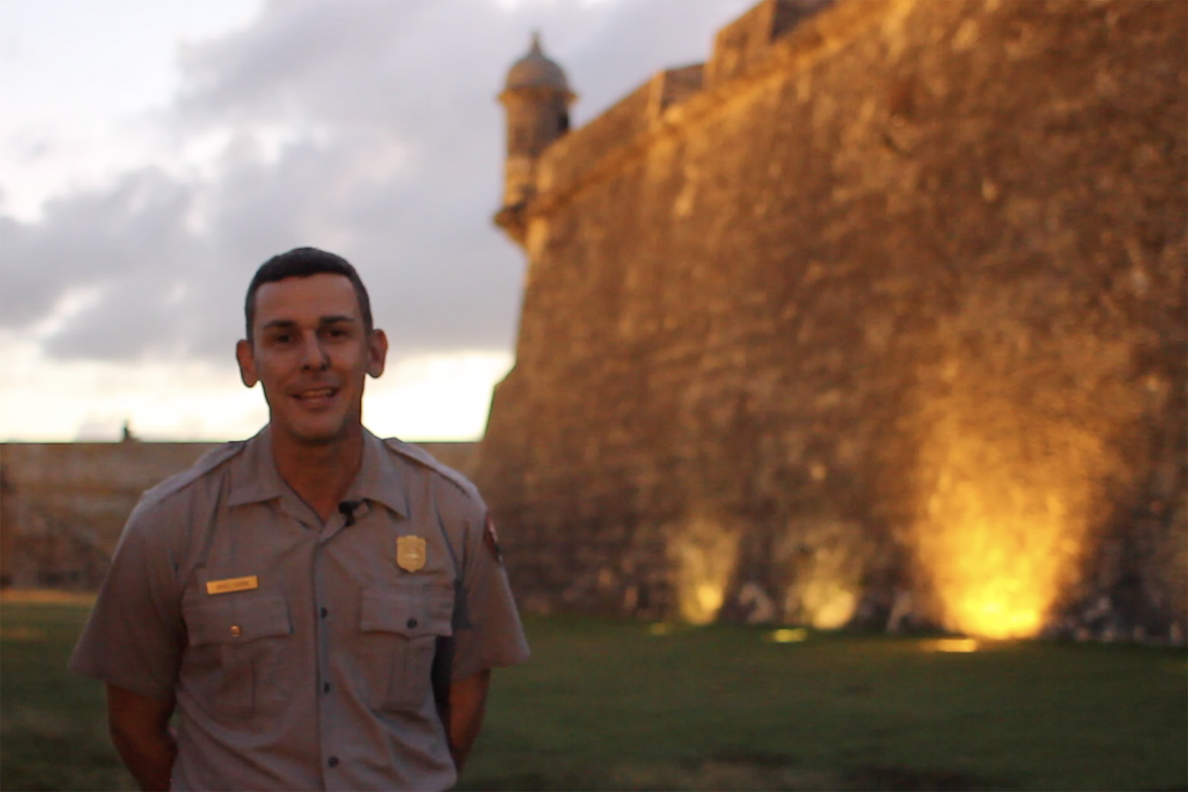 Special Permits Coordinator Angel Cuevas stands outside an illuminated San Juan National Historic Site