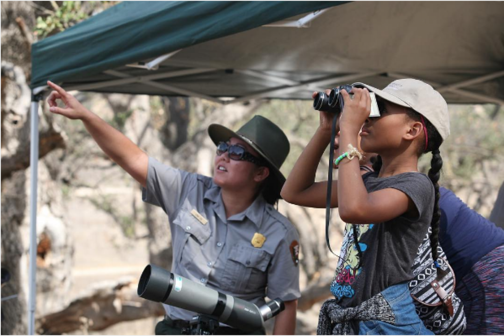 Park ranger pointing to sky while child looks through binoculars