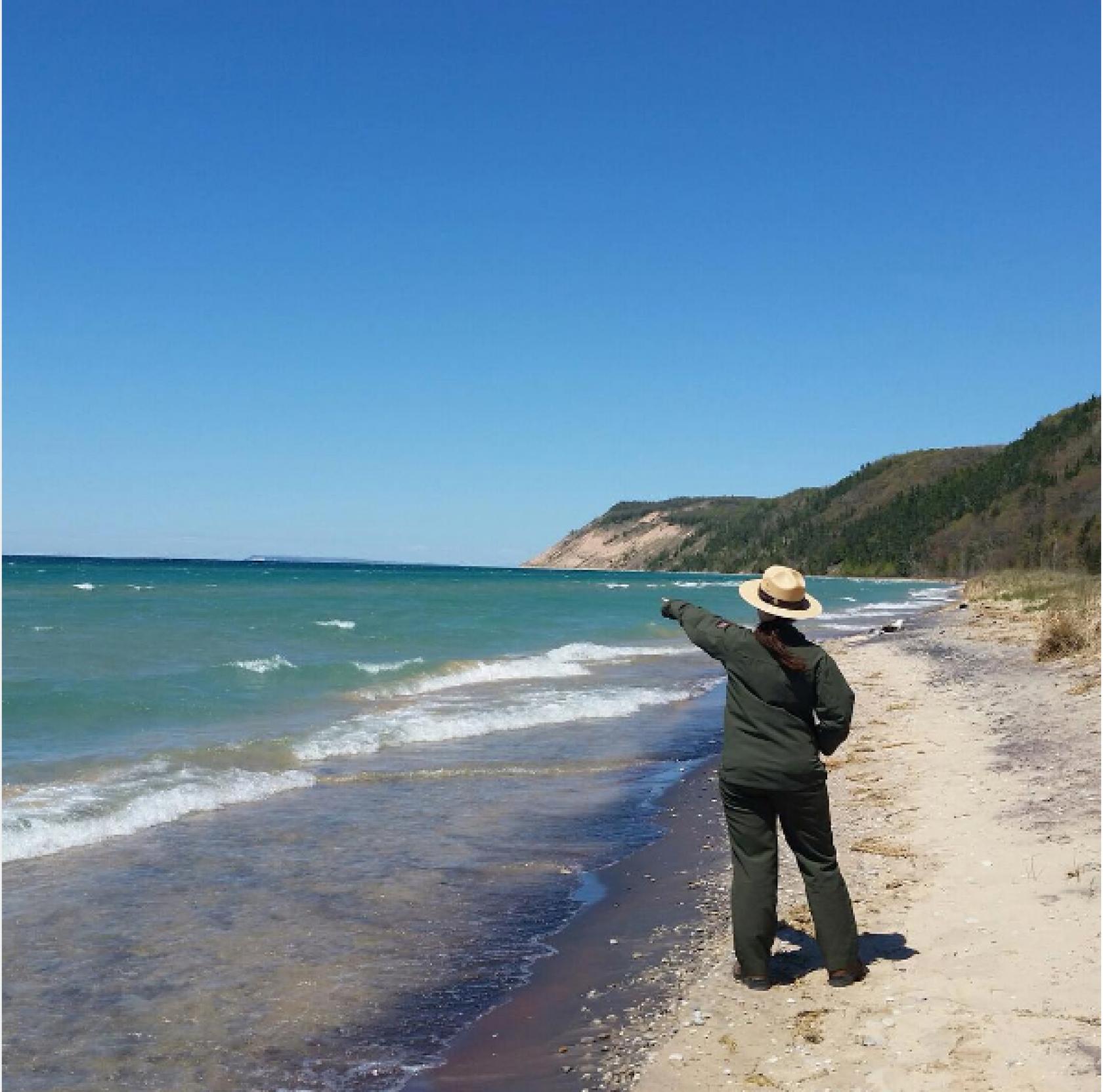 Park Ranger pointing at the shores of Lake Michigan and dunes at Sleeping Bear National Park
