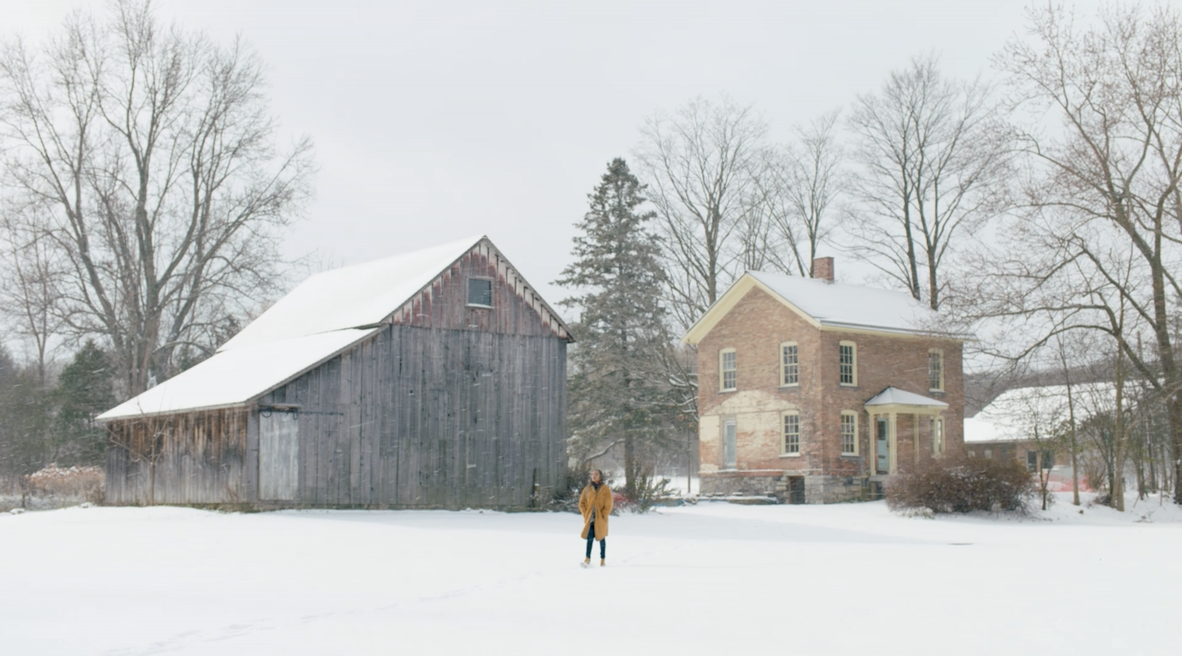 A visitor walks in the snow between a barn and two story brick building