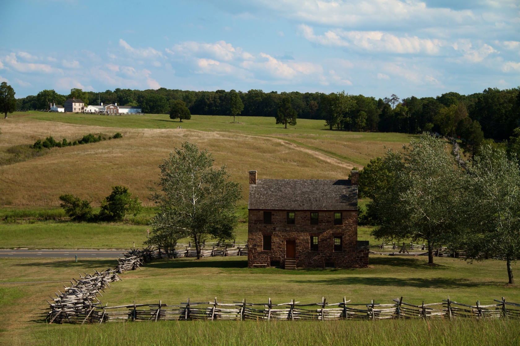 Virginia's Manassas National Battlefield Park, old stone house and trees line the green hills.