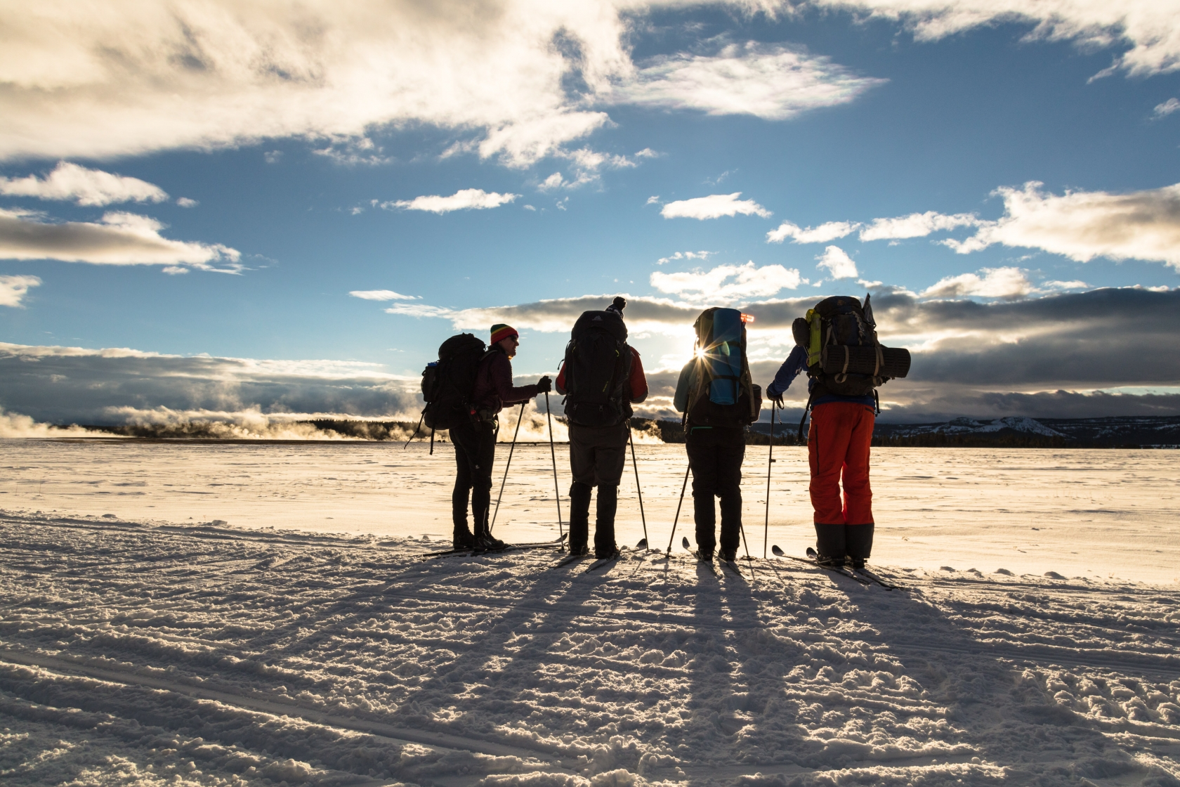 4 Backcountry skiers watching the sunset across the Lower Geyser Basin at Yellowstone National Park