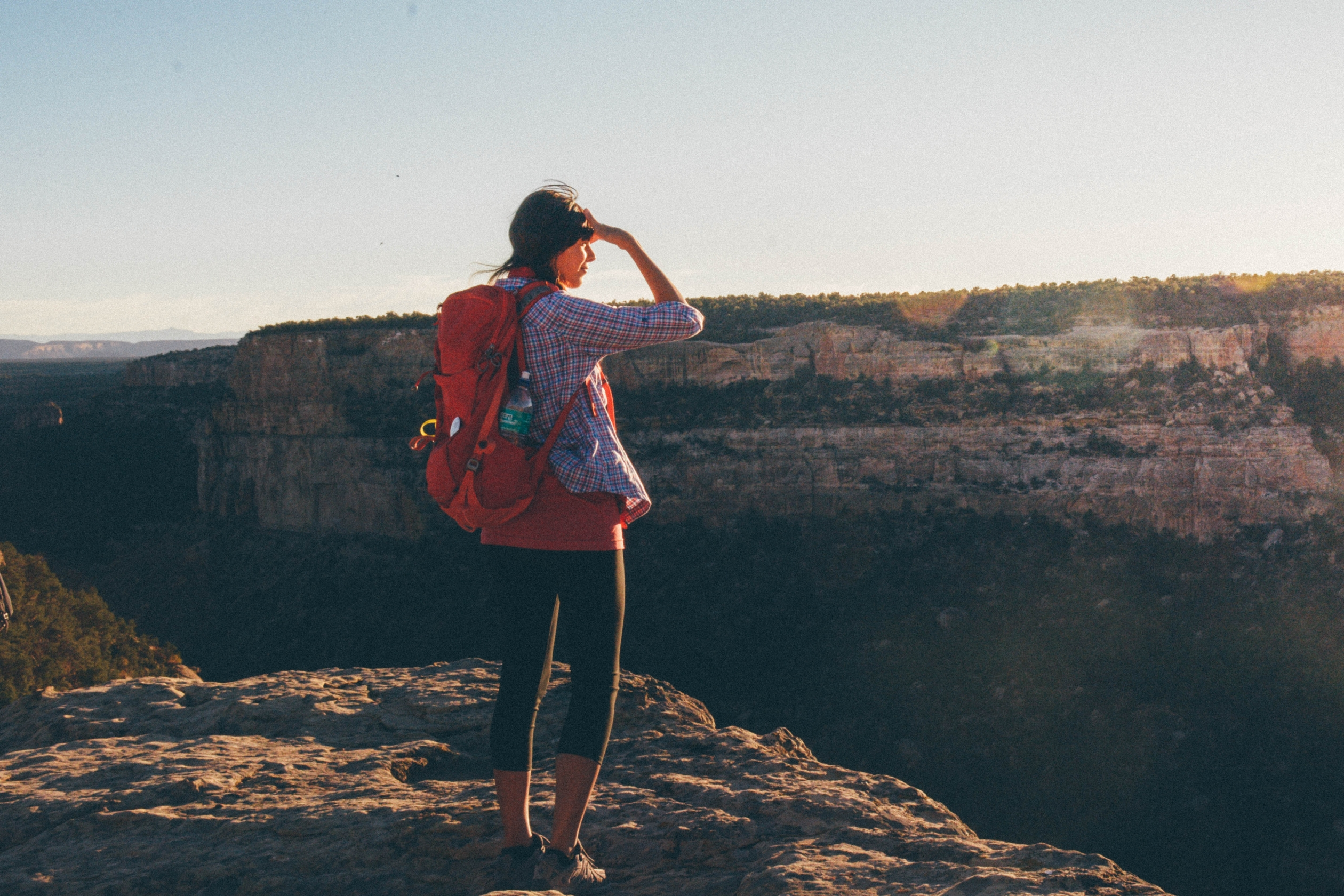 Woman With Red Backpack Looking Out Over Mesa Verde National Park