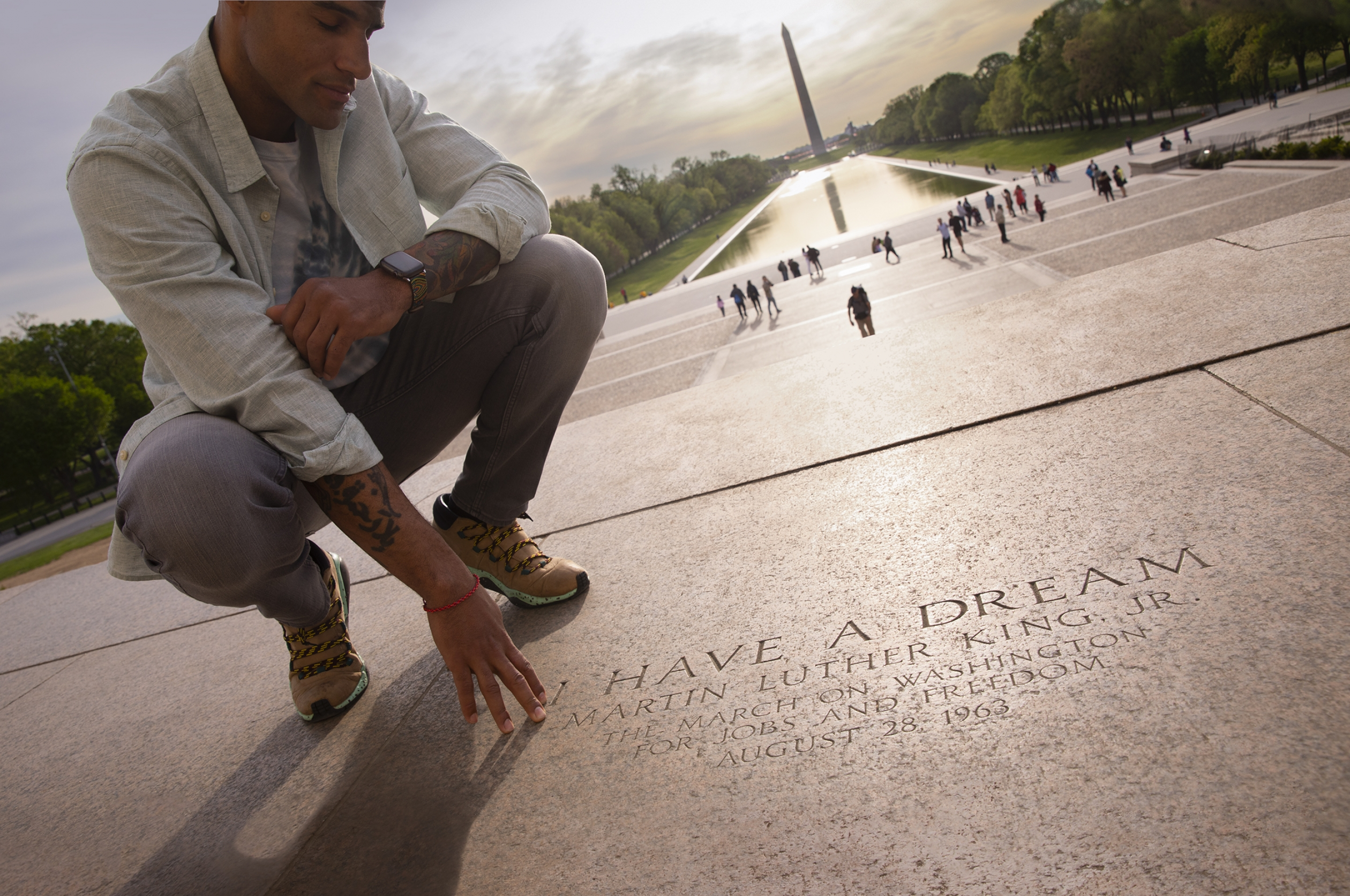 Man reading I Have a Dream inscription at the Lincoln Memorial with a view of the Washington Monument in the background.
