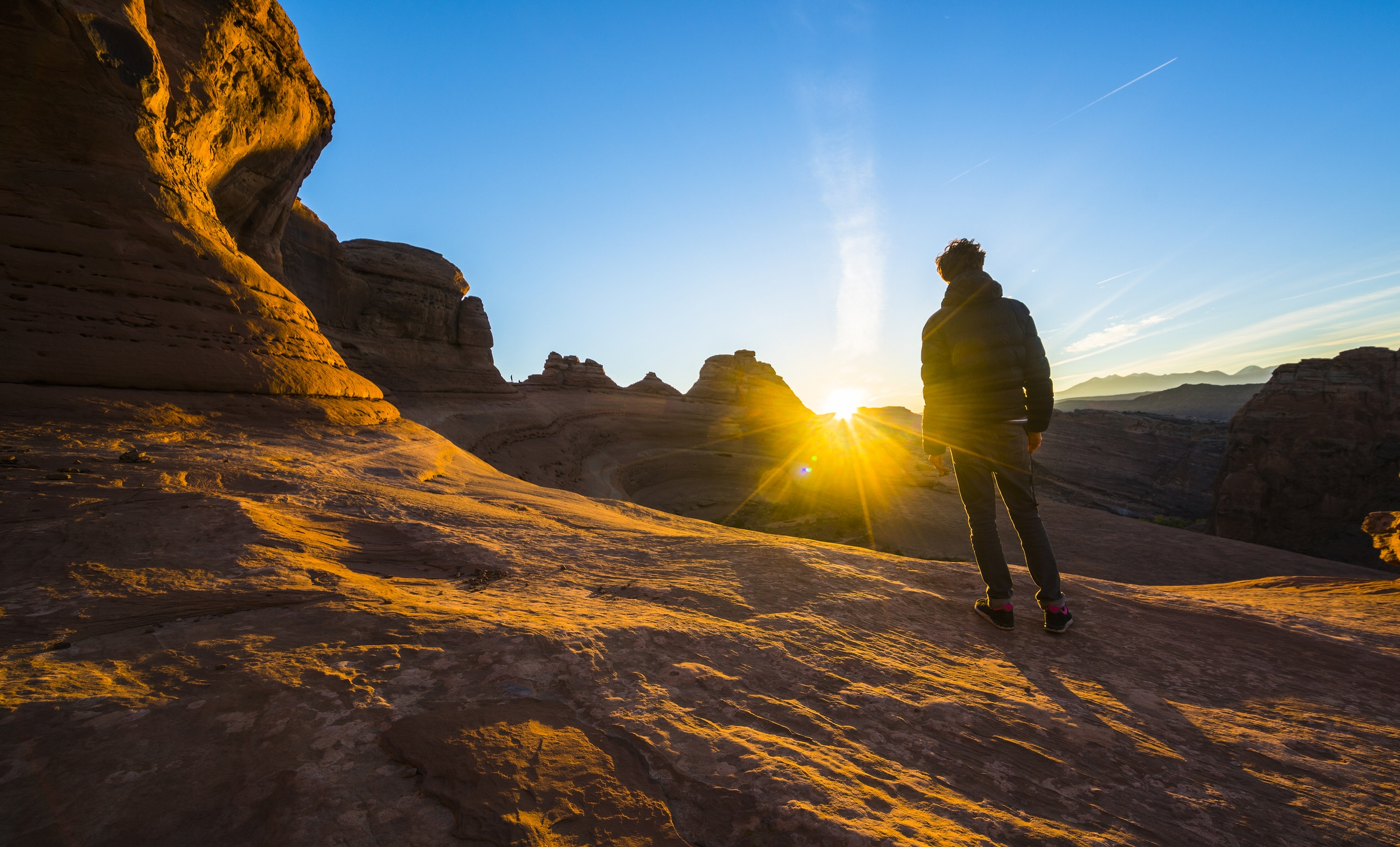 Man standing facing a setting sun at Arches National Park