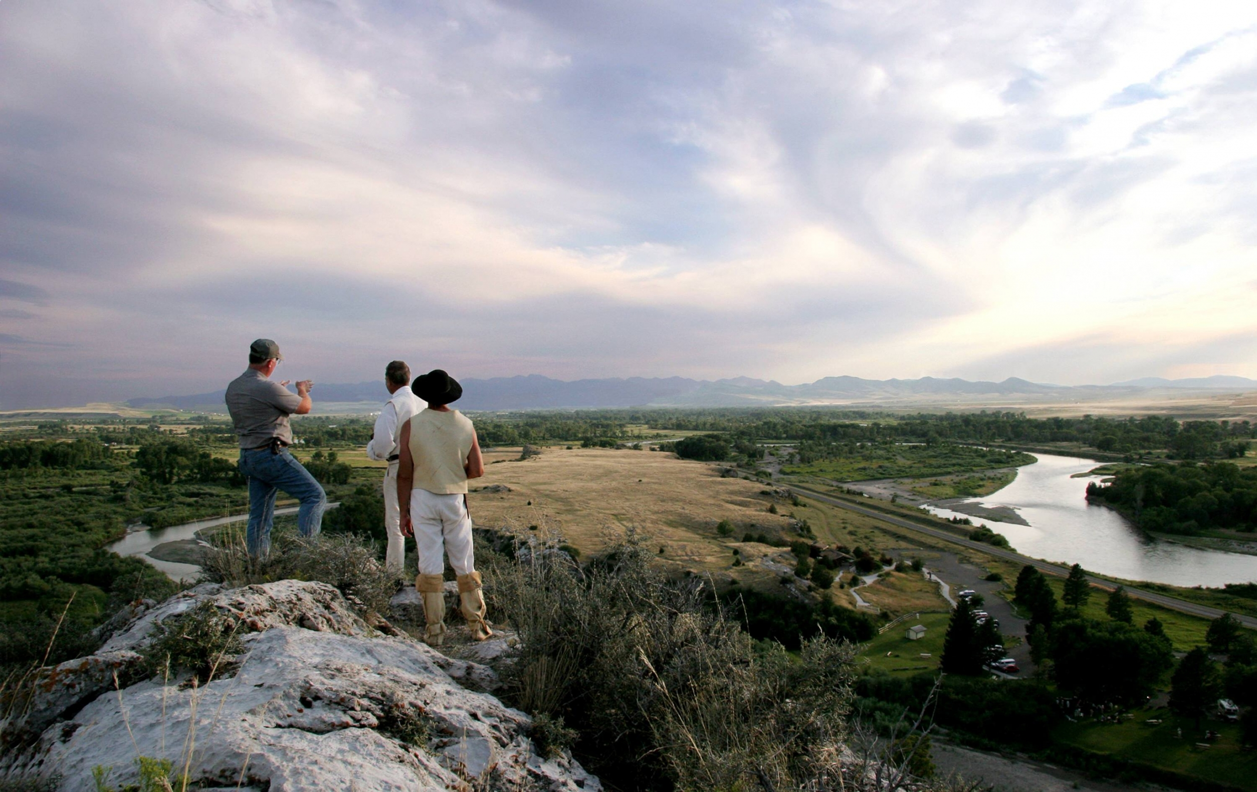 Tres hombres mirando a través de un valle verde con un río que lo atraviesa de un afloramiento de roca a lo largo del Sendero Histórico Nacional Lewis y Clark