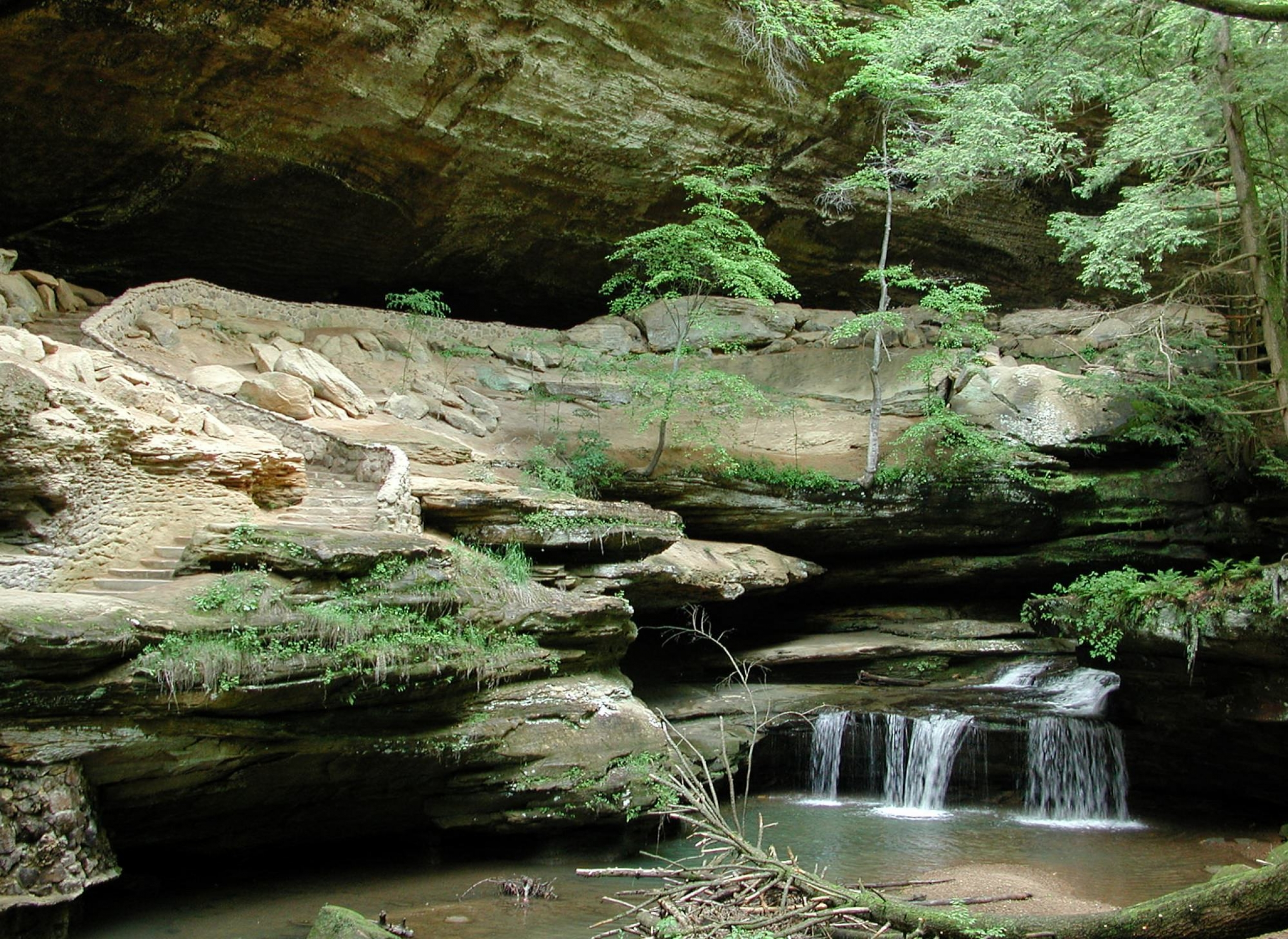 Small waterfall along a river srounded by sand-colored cliffs and green ferns in Ohio along the North Country National Scenic Trail