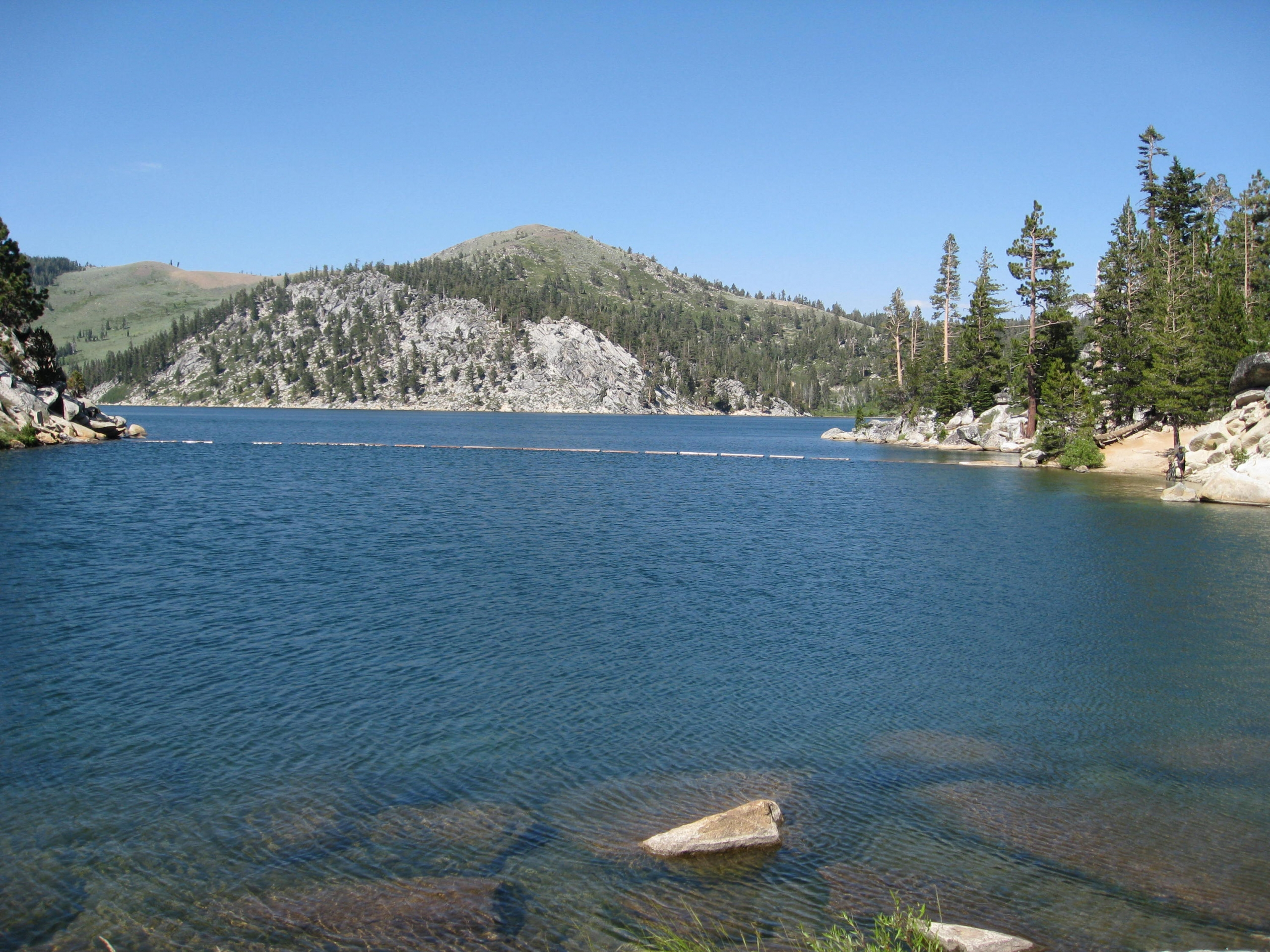 View across a blue lake sounded by grey granite mountains with evergreens at Marlette Lake along the Tahoe Rim Trail