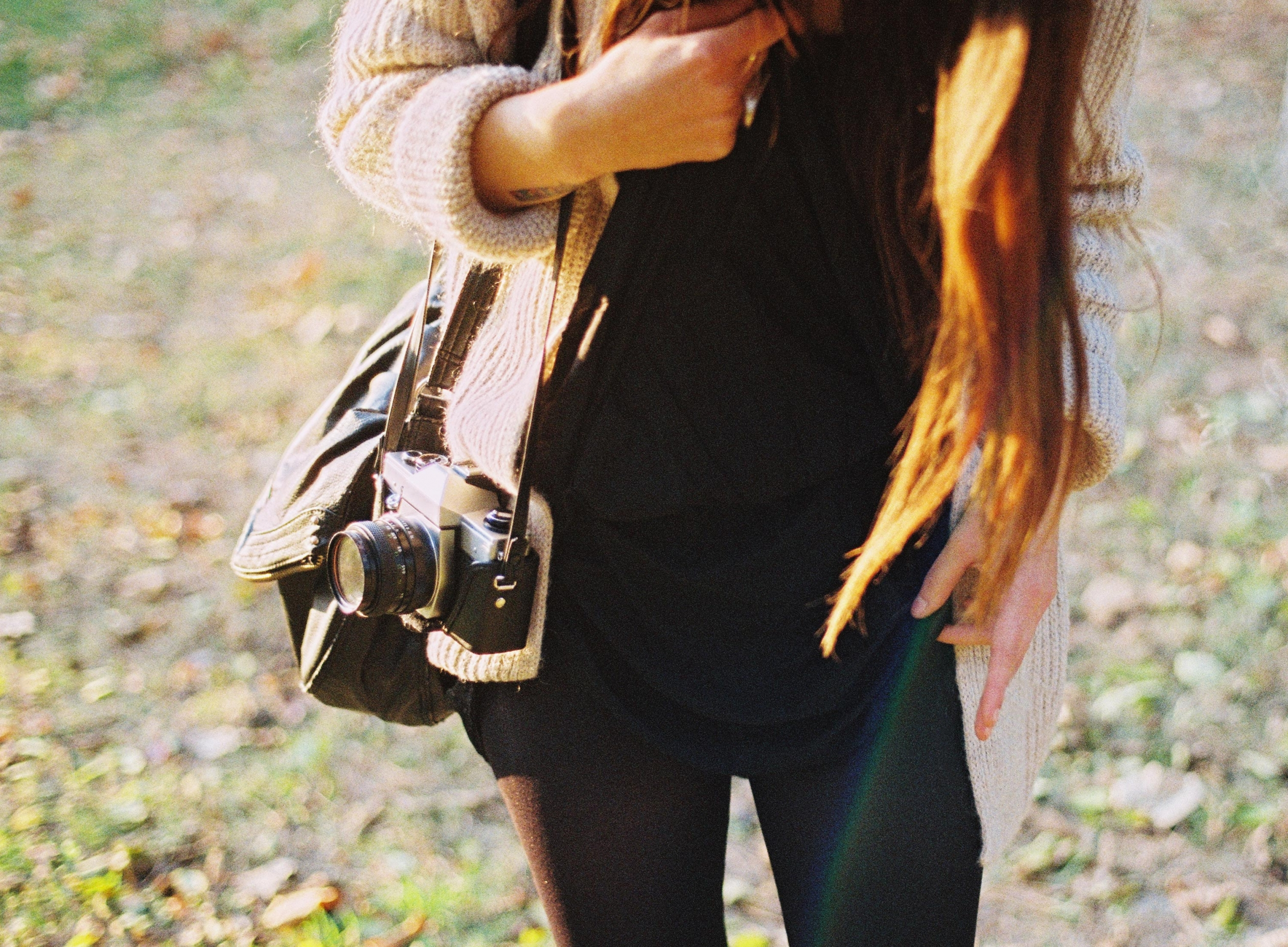 Woman holding a camera walking in a field
