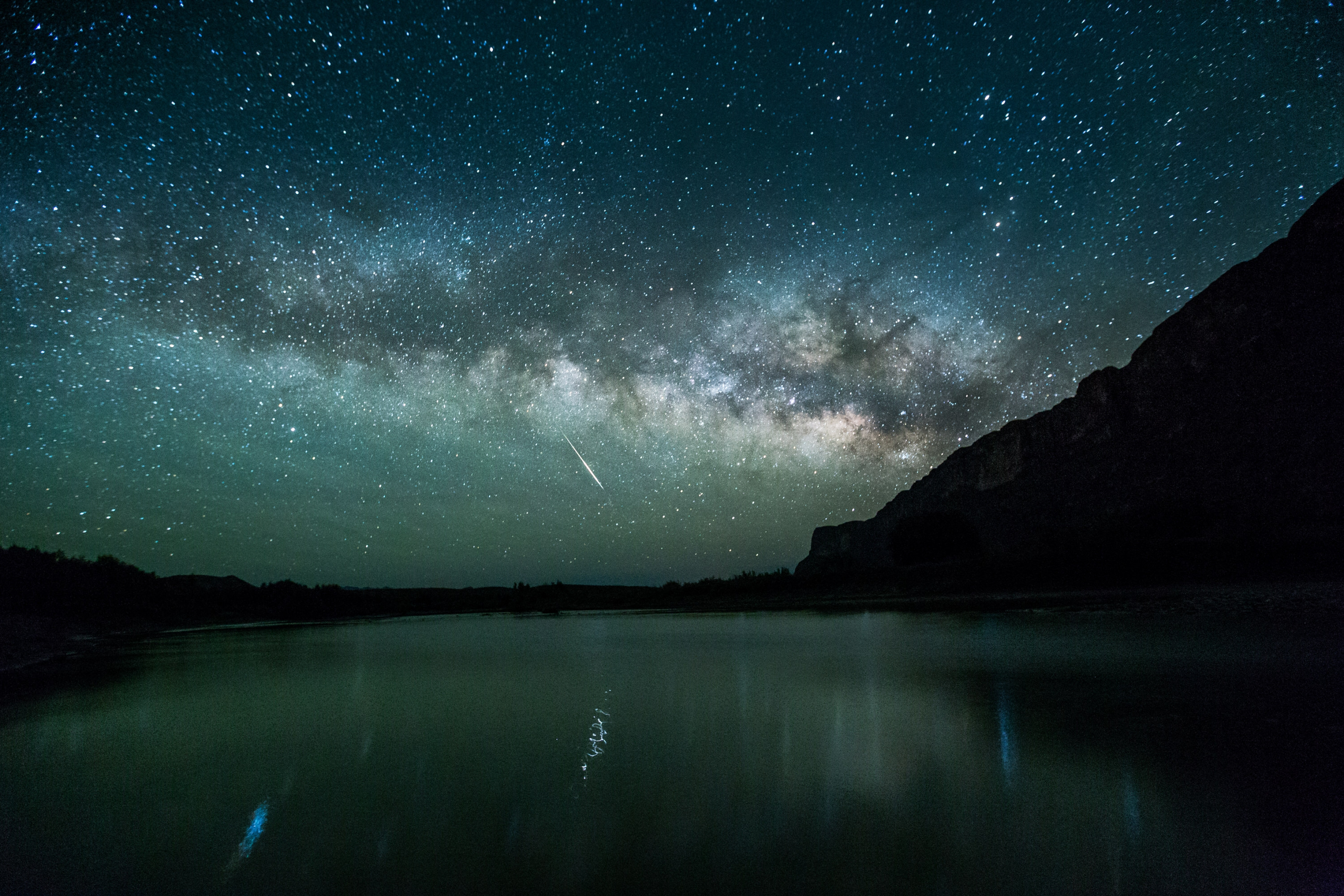 Green-blue Milky Way with a meteor over a lake in Santa Elena Canyon at Big Bend National Park