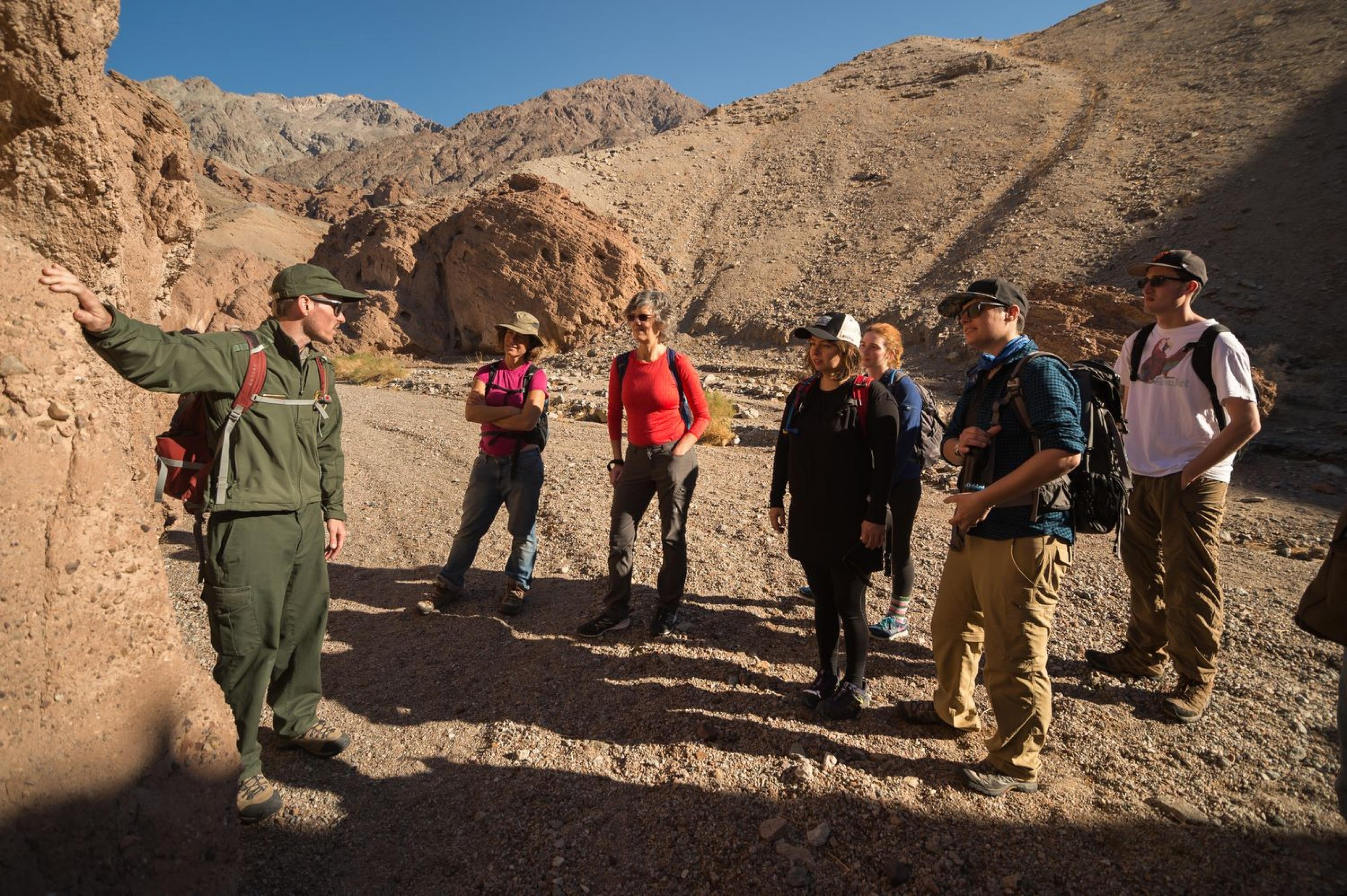 Un grupo de visitantes observando a un guardabosques apuntando a algo en las rocas en la gira de paleontología en el Parque Nacional del Valle de la Muerte