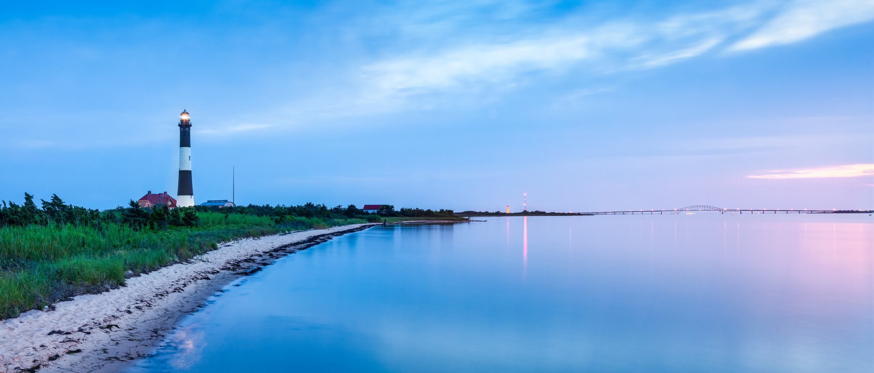 Blue dusk reflected into the ocean at the shore with a black and white lighthouse among greenery at Fire Islands National Seashore