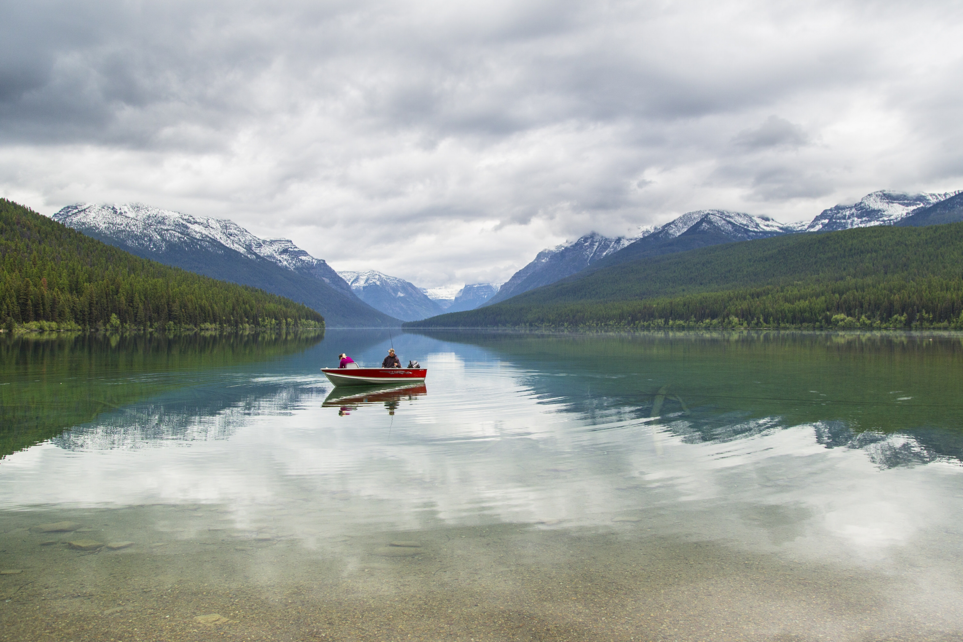 Boaters in a red boat on Bowman Lake at Glacier National Park