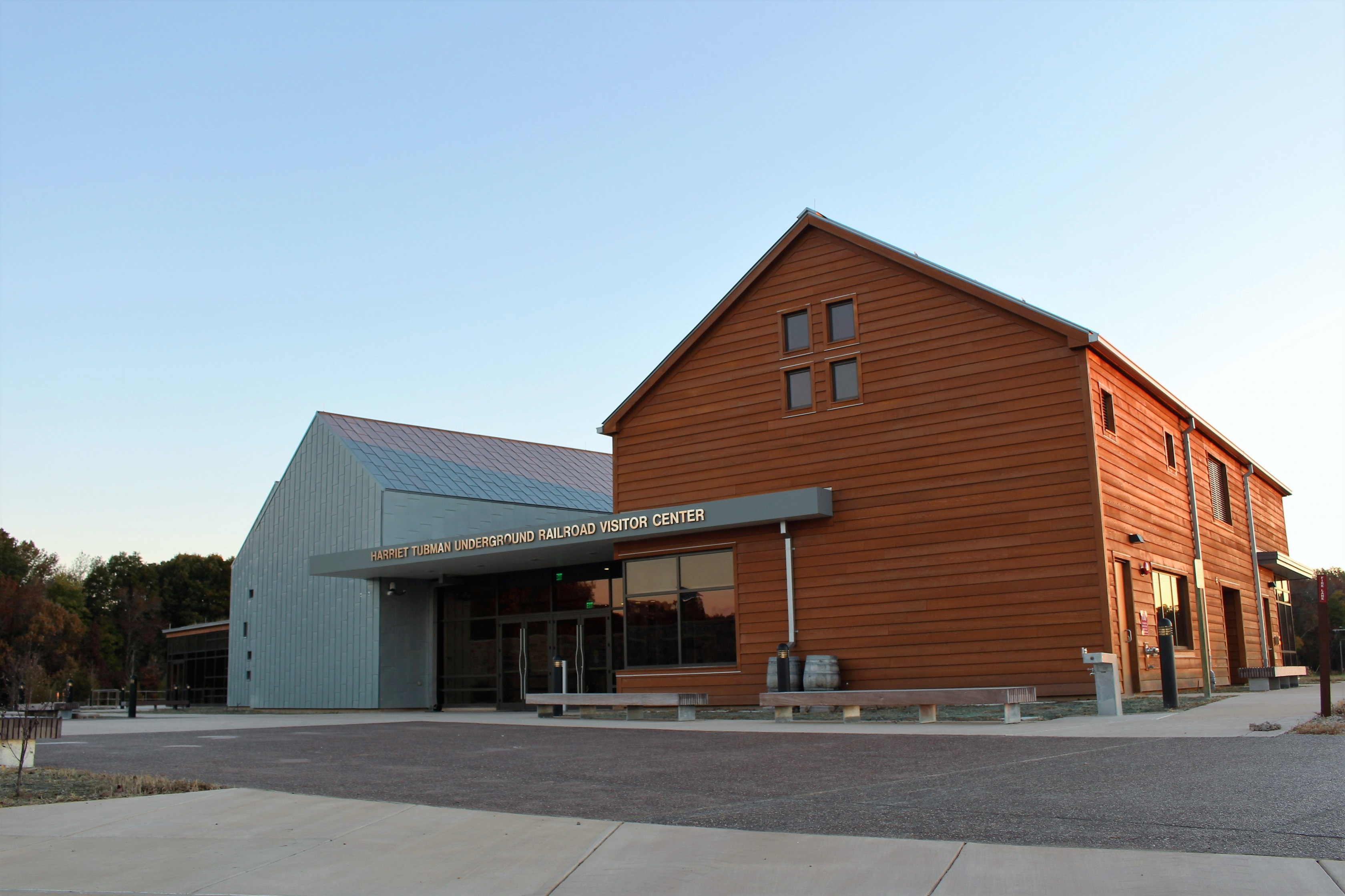 Front view of the visitor center, with two barn-like fronts visible, one in orange wood panel and one in metallic gray.